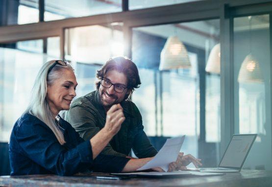 homem e mulher conversam animados em local de trabalho